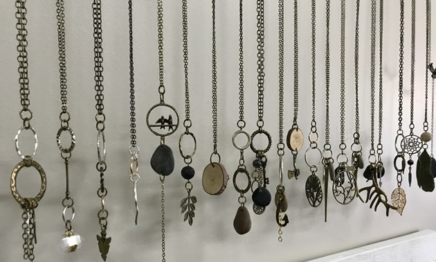 Necklaces are lined up and hanging on a wall. Many have charms and smooth river stones.