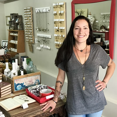 Owner Kara Clarke is standing in her store in front of lots of jewelry.