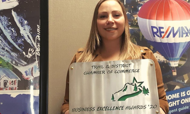 Katie Yuris holding Business Excellence Award