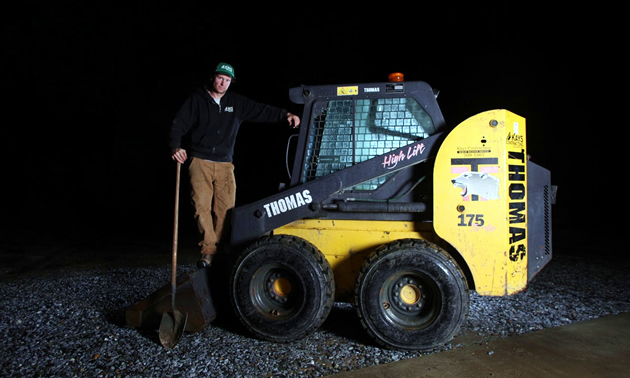 Owner of Kays Contracting, Matt Hanlon, poses with one of his contracting machines.