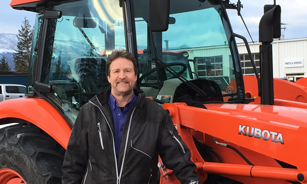Darrell Kemle standing in front of orange tractor.