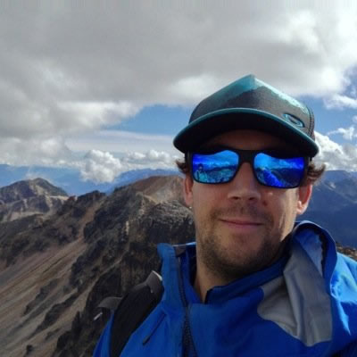 Andy Brown, new Communications and Social Media Coordinator standing on a mountain top