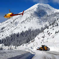 A helicopter hovers over an avalanche as a machine works to clear the road. A stunning mountain and blue sky are visible.