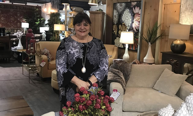 Kootenai Moon owner Valerie Semeniuk is sitting in her store with furniture and lamps in the background.