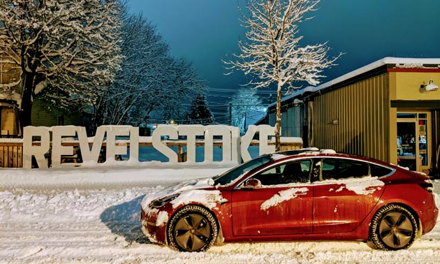Red electric car parked in front of Revelstoke sign.