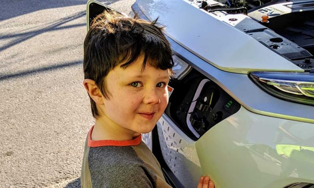 Child standing in front of electric car.