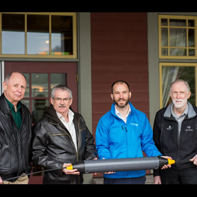 Columbia Basin Broadband Corporation Chief Operating Officer, Dave Lampron, Kaslo Infonet Society (KiN) President Don Scarlett, KiN Board Member Tim Ryan together with Robert Abbey, Assistant Manager of the Kaslo Hotel, showcase a section of fibre optik cable similar to the one used in this project. (Left to right: Don, Robert, Dave, Tim)