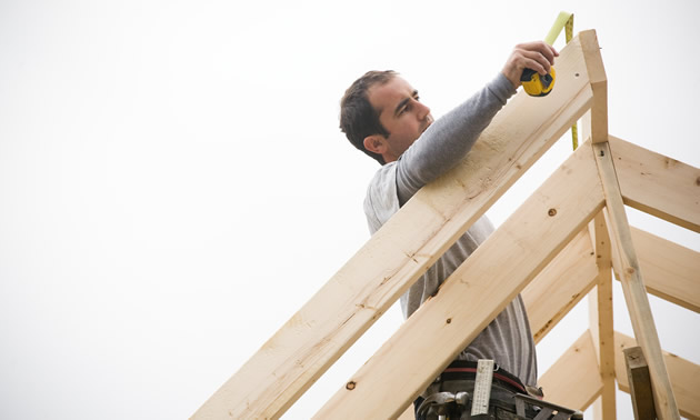 Man measuring a roof truss.