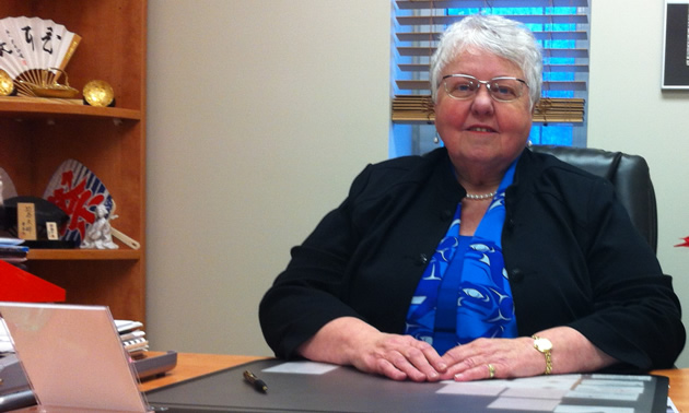 Grey-haired woman sitting at a desk