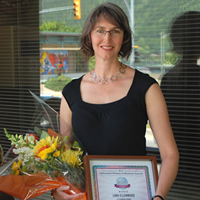 Lara Ellenwood of Ellenwood Homes stands with a bouquet and her Influential Women in Business Award certificate.