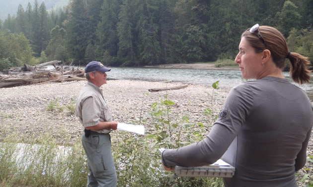A man and a woman, both holding documents, survey a stretch of river