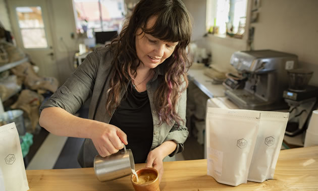 Ilana Cameron, owner of Lark Coffee, pouring a cup of coffee.