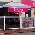 Pink awnings with white lettering shelter the restaurant entry and windows.