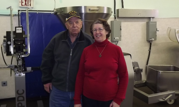 Man and woman in front of machinery