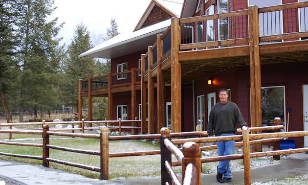 Man standing in front of large building in the Rocky Mountains