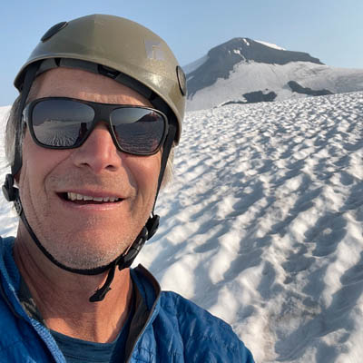 """Powder Matt"" Mosteller looking into camera, snowy mountain in background."