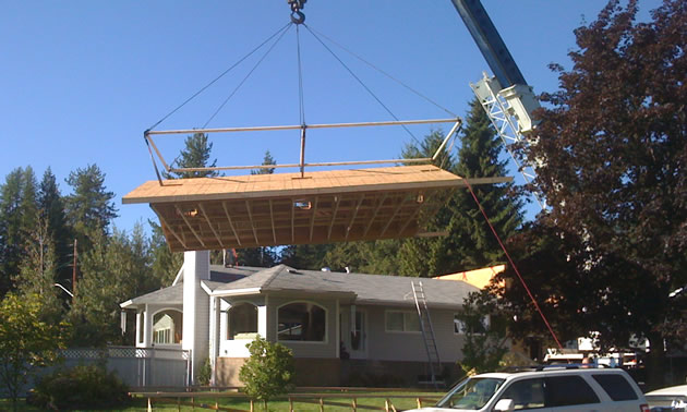 A crane lifts a constructed roof onto the house it's intended for.