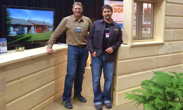 Aaron Fanderl and Max Cameron stand outside their wall display at a tradeshow.