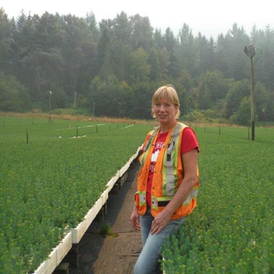 Melanie Buerge is standing outside in a row that is between huge benches of evergreen tree seedlings.