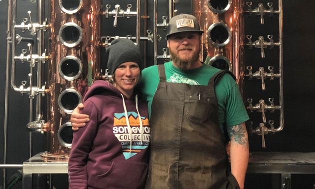Jennifer and Josh McLafferty standing in front of distillery.
