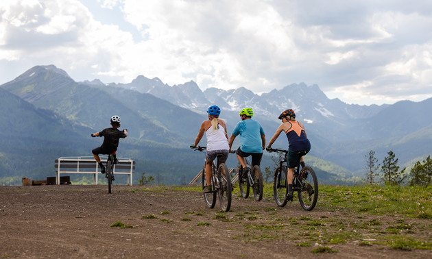 Four mountain bikers approach a viewpoint with a vista of mountains