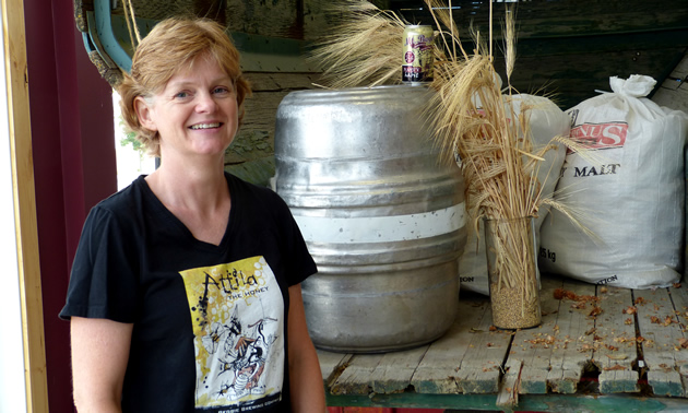 Tracey Larson stands by a vintage truck bed that features a keg, brewing grains, and a can of beer by Mt. Begbie Brewing Co.