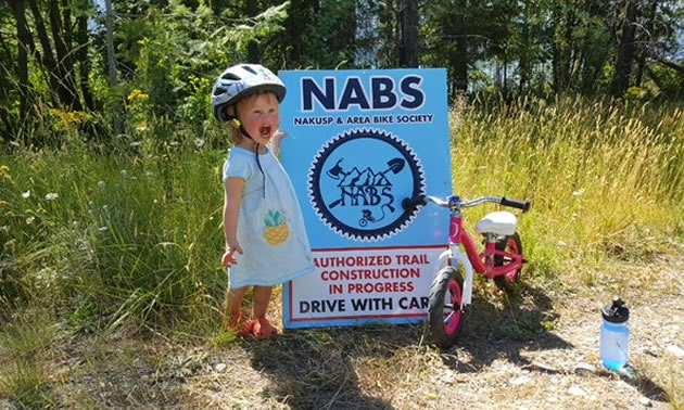 Little Nieve Thomas standing in front of a NABS construction sign.