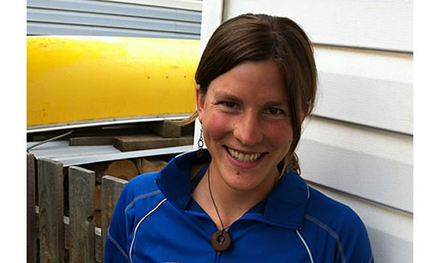 A brown haired young woman smiles at the camera. She wears a blue BC shirt and there is a yellow canoe in the background.