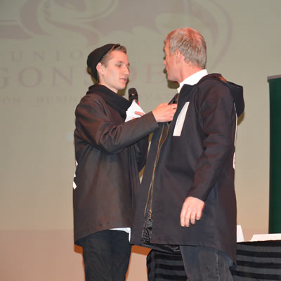 Nathan Staplin has the MC of Junior Dragon's Den, Glen Hicks, try on a Black Dust Apparel jacket.