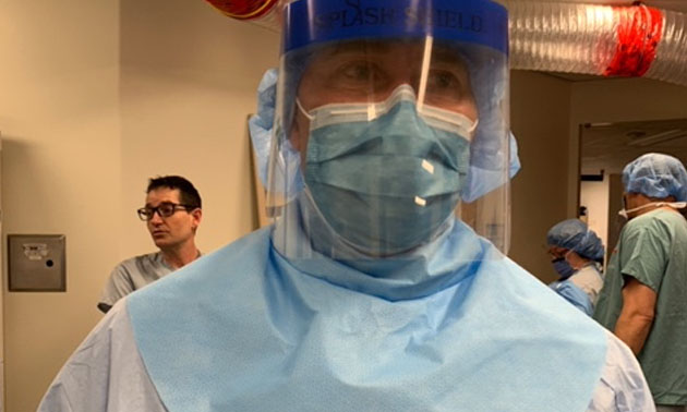 Medical doctor wearing neck guard and face shield.