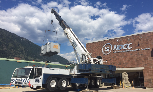 Craning the air handling unit onto the roof of the community complex.