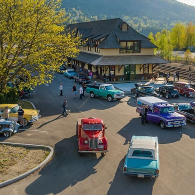 Nelson & District Chamber of Commerce building, with classic and vintage cars in parking lot.