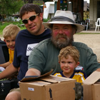 A senior man drives a yellow quad carrying his son and three little grandsons.