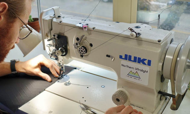 Worker sitting at Juki industrial sewing machine, sewing fabric.