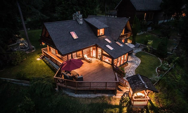 Aerial view of large home lit up at night.