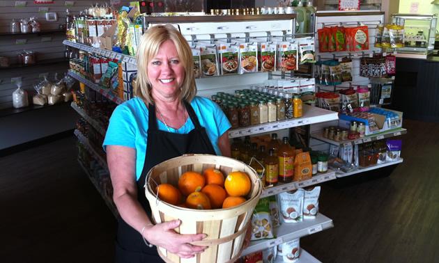 Photo of woman holding large basket of fruit