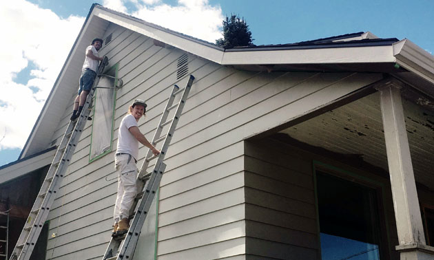 Joel Godbee on ladder painting side of house.