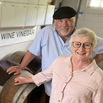 Patrick and Loie Robertson standing beside vinegar barrels.