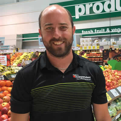 Brian Pealow, owner of Pealow's grocery store, stands in the produce aisle.