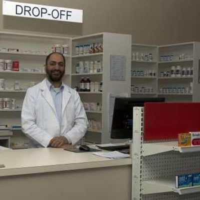 Ahmed Elmaddah standing behind pharmacy counter.