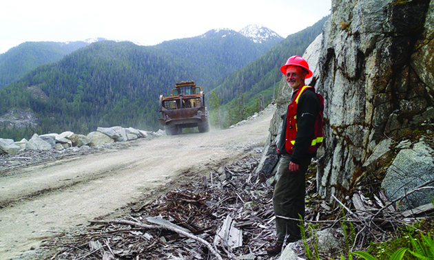 A worker stands next to a forestry road in the bush in British Columbia with heavy equipment in the background.
