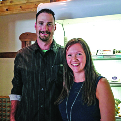 The two owners, Matthew Harris and Ella Markan, stand in front of a cheese case.