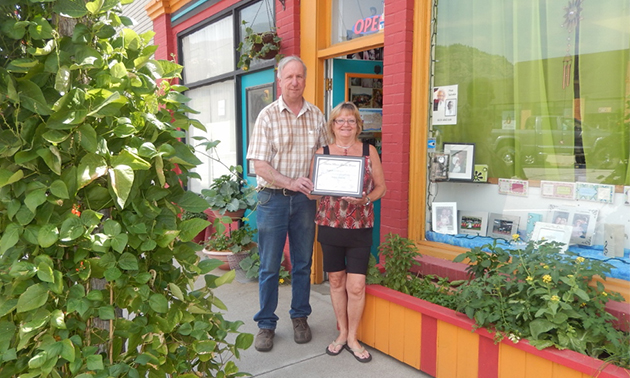 Rob Ironmonger of Keystone Appraisals hands an award to Darlene Paulson of Doell Photo in Trail for her outstanding edible planters.