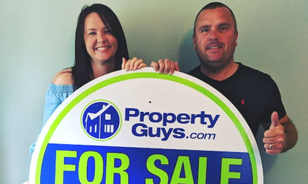 Andy and Sinead Britner stand behind Property Guys SOLD sign.