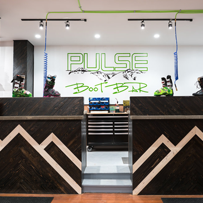 Store front at Pulse Boot Lab and Ski Co., showing wooden front desk and 'boot bar' beyond.
