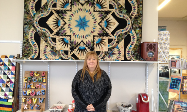 Denise Nagai is standing in front of a beautilful quilt with geometric designs.