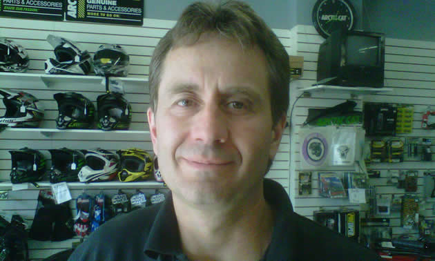 Close-up of smiling man with a merchandise display wall in the background