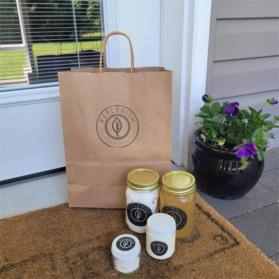A brown paper bag sitting on a doorstep, with Replenish products arranged in front of the bag.