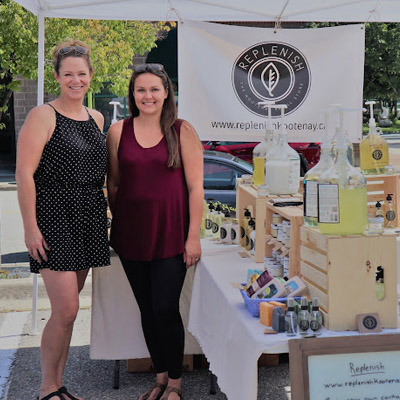 Melinda Nealis and Kayla Carley standing in front of their farmers market booth.