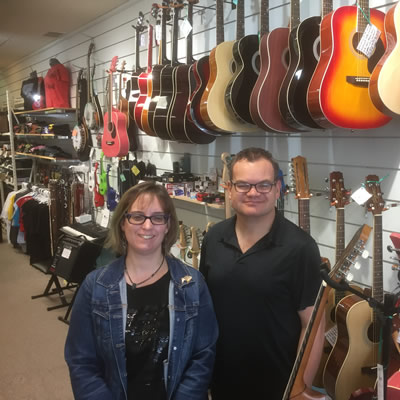 Jeremy and Felicity Youngward standing in their music store, with row of guitars behind them.